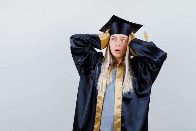 Blondynka w sukni ukończenia szkoły i czapce trzymająca ręce na skroniach, patrząca na lewą stronę i wyglądająca na zaskoczoną