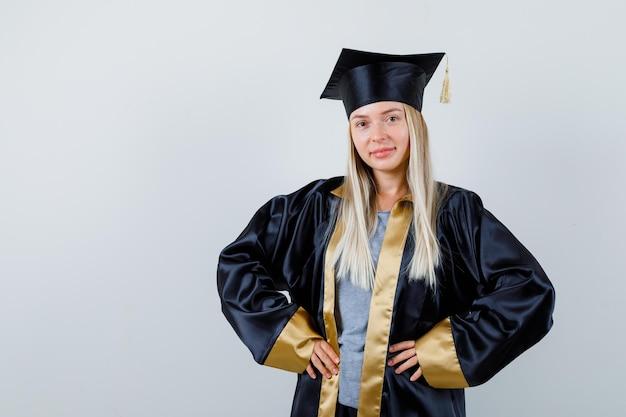 Blondynka w sukni ukończenia szkoły i czapce, trzymająca się za ręce w talii i wyglądająca na szczęśliwą