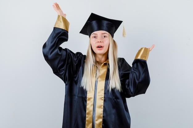 Blondynka w sukni ukończenia szkoły i czapce wyciąga ręce w pytający sposób i wygląda na szczęśliwą