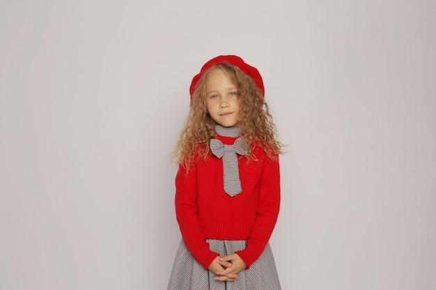 Blondynka w szkolnym garniturze szara sukienka i czerwony sweter czerwony beret emocje
