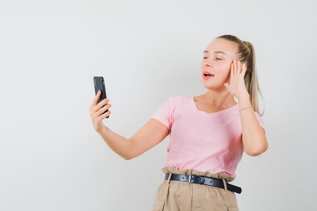 Blondynka w t-shirt, spodnie pokazujące dłoń na czacie wideo i wyglądająca pewnie, widok z przodu.