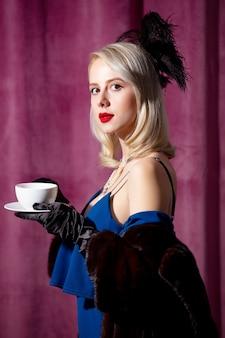 Blondynka w vintage niebieska sukienka i futro z filiżanką kawy