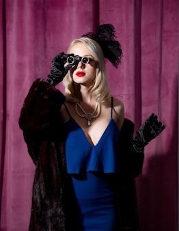 Blondynka w vintage niebieska sukienka i futro z okularami opera