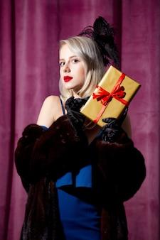 Blondynka w vintage niebieska sukienka i futro z pudełkiem