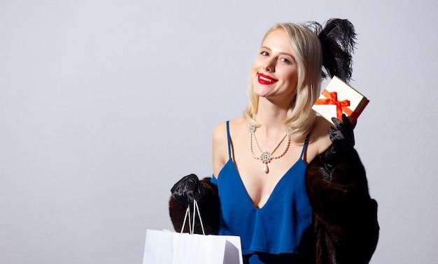 Blondynka w vintage niebieska sukienka i futro z pudełko i torby na zakupy