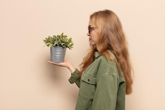 Blondynka w widoku profilu chce skopiować przestrzeń do przodu, myśleć, wyobrażać sobie lub marzyć