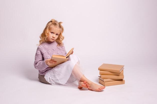 Blondynka w wieku przedszkolnym siedzi na białym tle z książką w ręku, uśmiechając się, myśląc