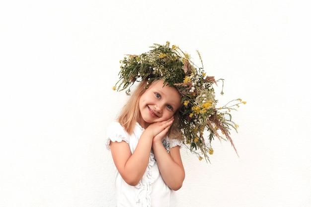 Blondynka w wieńcu z polnych kwiatów przechyliła głowę na bok