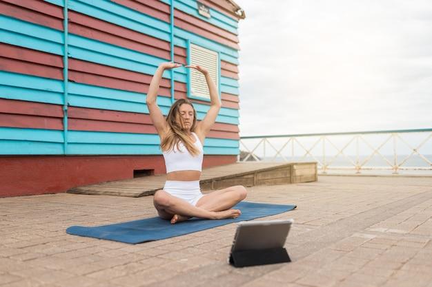 Blondynka w zajęciach jogi online z białą odzież sportową. na tle czerwono-niebieskiej kabiny nad morzem