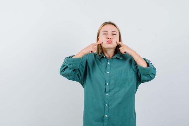 Blondynka w zielonej bluzce nadyma policzki, wskazując ją palcem wskazującym i wygląda ładnie