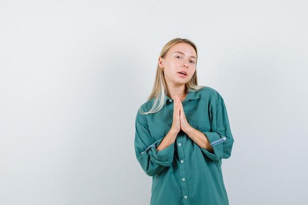Blondynka w zielonej bluzce pokazująca gest namaste i wyglądająca na szczęśliwą