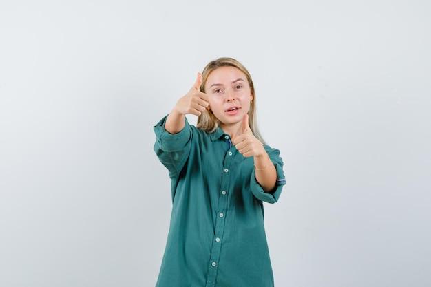 Blondynka w zielonej bluzce pokazująca kciuki do góry obiema rękami i wyglądająca ładnie