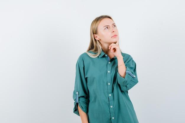 Blondynka w zielonej bluzce stojąca w pozie do myślenia i patrząca zamyślona
