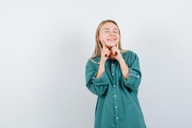 Blondynka w zielonej bluzce trzymająca palce wskazujące przy ustach, zmuszając się do uśmiechu i wyglądając na szczęśliwą