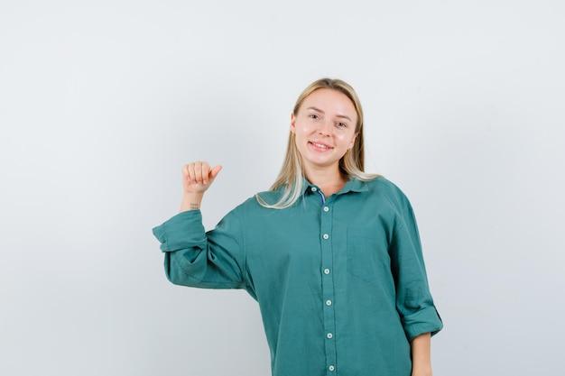 Blondynka w zielonej bluzce zaciska pięść i wygląda na szczęśliwą