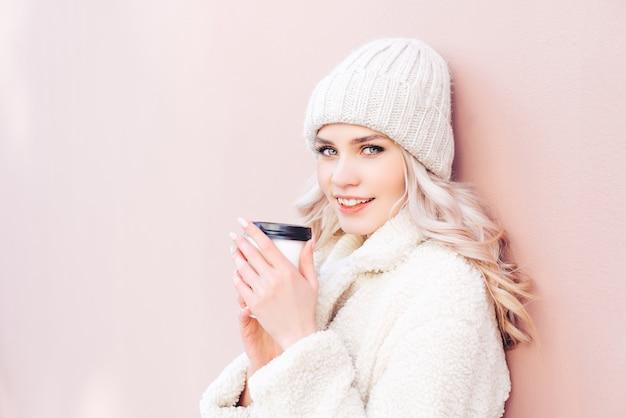 Blondynka w zimowe ubrania trzyma kawę w papierowej filiżance na różowym tle. młoda kobieta uśmiechnięta i patrzeje kamerę.