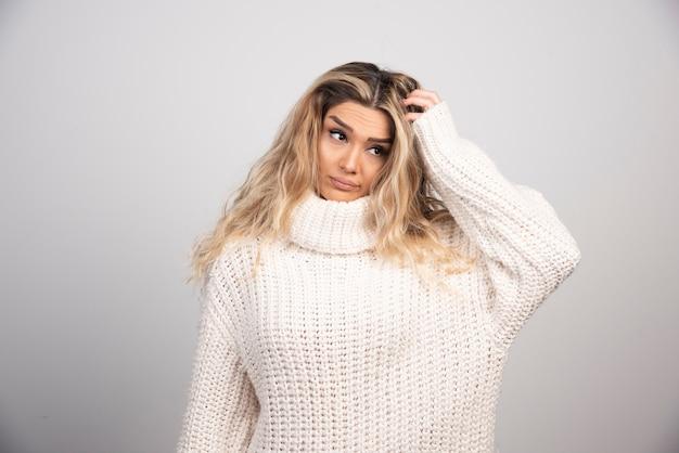 Blondynka w zimowy strój drapie się po włosach.