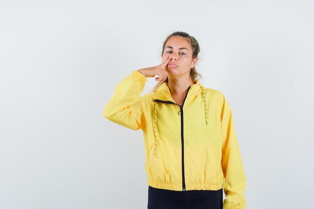 Blondynka w żółtej bomberce i czarnych spodniach kładzie palec na nosie i wygląda ładnie