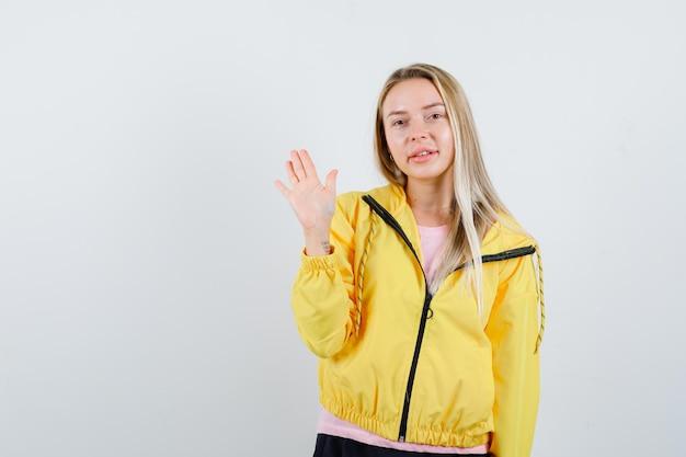 Blondynka w żółtej kurtce macha ręką na powitanie i wygląda atrakcyjnie