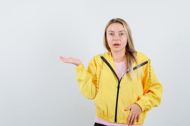 Blondynka w żółtej kurtce robi powitalny gest i wygląda kusząco