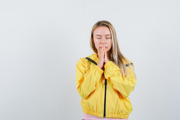 Blondynka w żółtej kurtce trzymająca się za ręce w geście modlitwy i patrząca z nadzieją