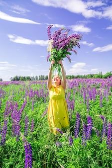 Blondynka w żółtej sukience w łubinowym polu. letni słoneczny dzień. relaks, wakacje, koncepcja wolności.