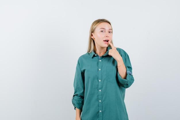 Blondynka wkłada palec wskazujący do ust w zielonej bluzce i wygląda na zaskoczoną