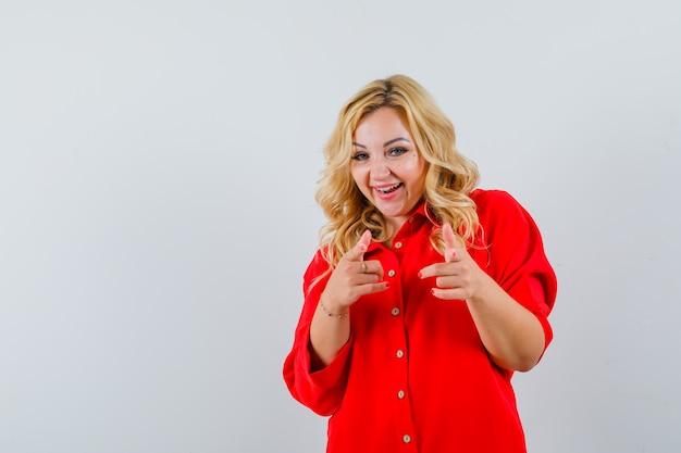 Blondynka, wskazując na aparat palcami wskazującymi w czerwonej bluzce i patrząc szczęśliwy.