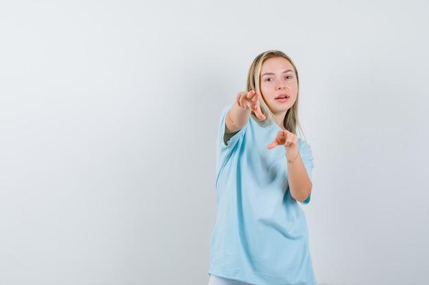 Blondynka, wskazując na aparat palcami wskazującymi w niebieskiej koszulce i patrząc pewnie, z przodu.