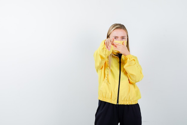 Blondynka, wskazując na aparat, trzymając dłoń na ustach w dresie, masce i wyglądając na zaniepokojoną. przedni widok.