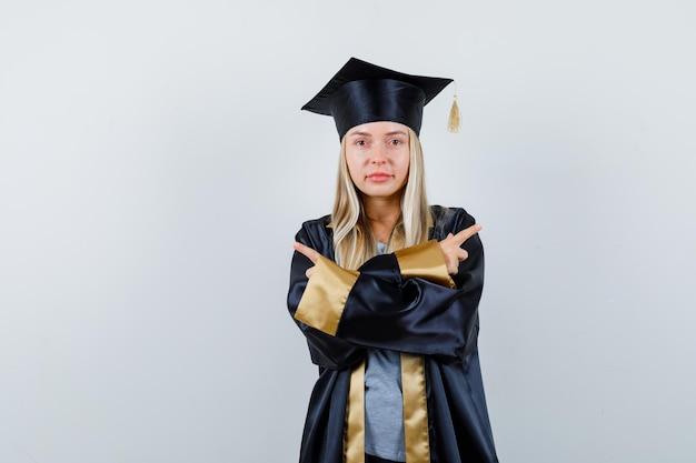 Blondynka wskazując przeciwne kierunki w sukni i czapce ukończenia szkoły i patrząc poważnie.