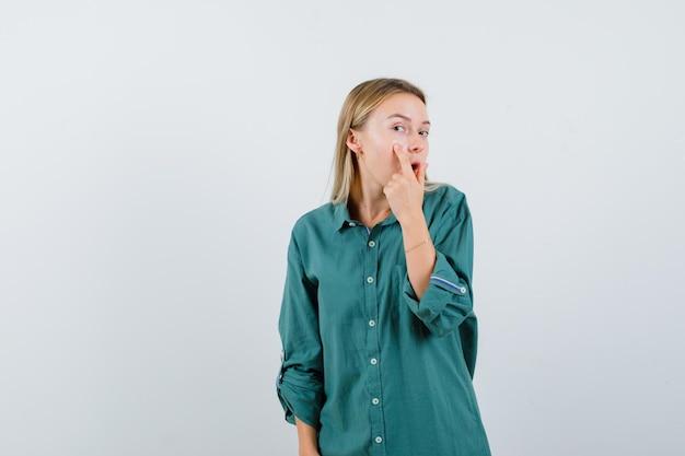 Blondynka wskazując twarz palcem wskazującym w zielonej bluzce i patrząc skupiony.
