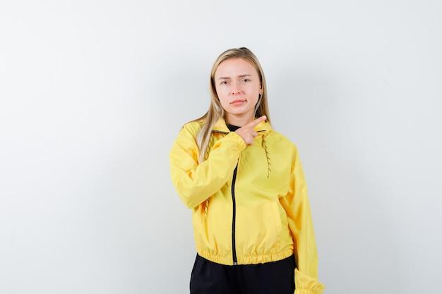 Blondynka wskazująca prosto w dres i wyglądająca poważnie. przedni widok.