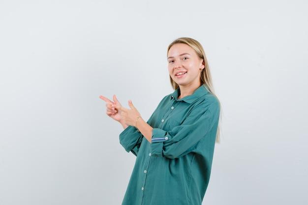 Blondynka wskazująca w lewo palcami wskazującymi w zielonej bluzce i wyglądająca na szczęśliwą
