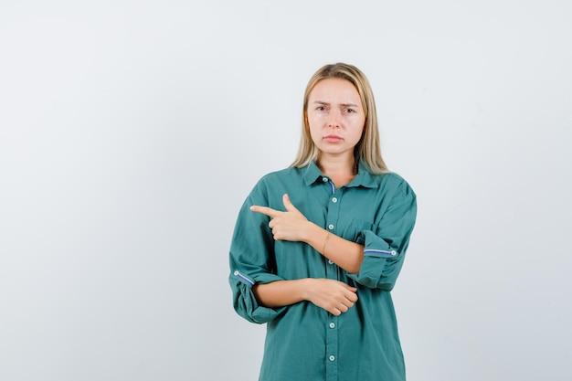 Blondynka wskazująca w lewo palcem wskazującym w zielonej bluzce i wyglądająca na zirytowaną