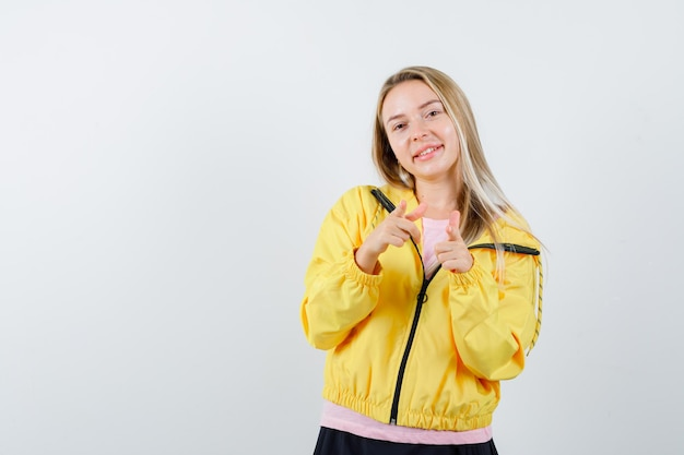 Blondynka wskazuje na aparat palcami wskazującymi w różowej koszulce i żółtej kurtce i wygląda poważnie