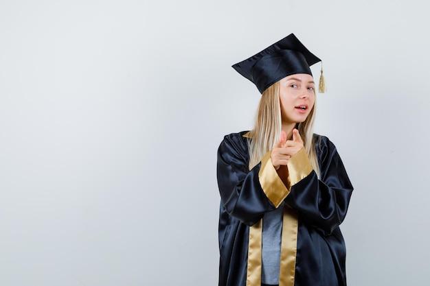 Blondynka wskazuje na aparat palcami wskazującymi w sukni i czapce ukończenia szkoły i wygląda na szczęśliwą