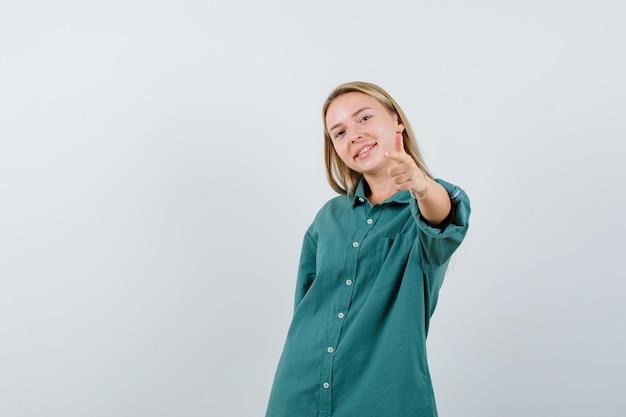 Blondynka wskazuje na aparat palcami wskazującymi w zielonej bluzce i wygląda na szczęśliwą