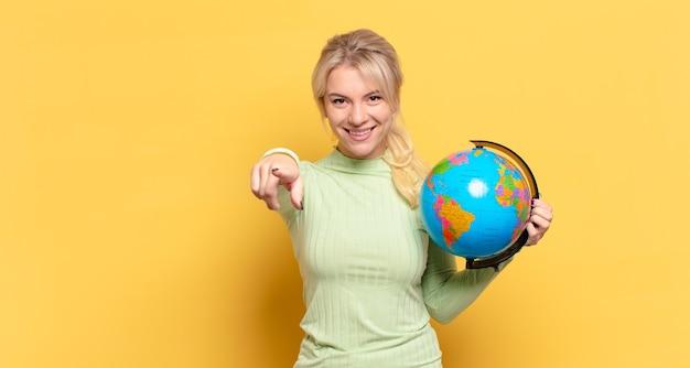 Blondynka wskazuje na przód z zadowolonym, pewnym siebie, przyjaznym uśmiechem, wybiera ciebie