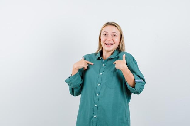 Blondynka wskazuje na siebie palcami wskazującymi w zielonej bluzce i wygląda na szczęśliwą