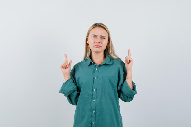Blondynka wskazuje palcem wskazującym w zielonej bluzce i wygląda na zirytowaną
