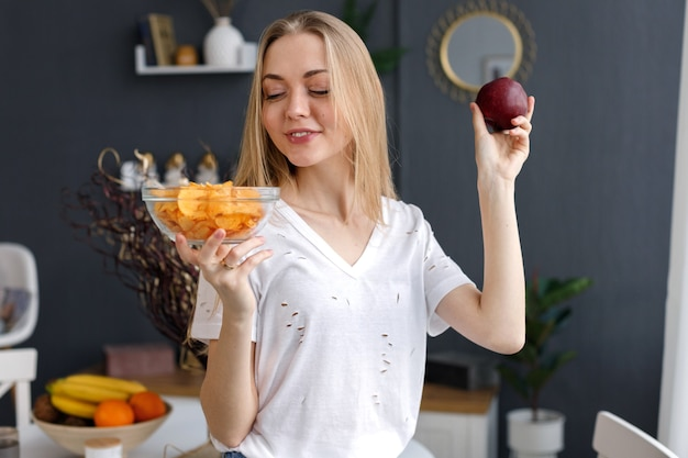 Blondynka wybiera w domu frytki i jabłko