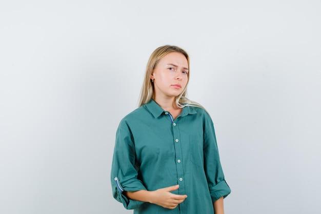 Blondynka wyciąga jedną rękę trzymając coś w zielonej bluzce i wygląda poważnie
