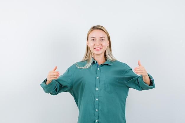Blondynka wyciąga ręce trzymając coś w zielonej bluzce i wygląda na szczęśliwą