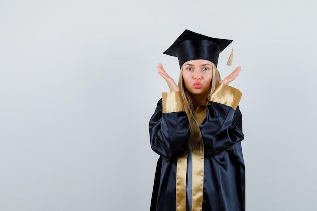 Blondynka wyciąga ręce w pobliżu twarzy, wysyła pocałunki w sukni i czapce ukończenia szkoły i wygląda na szczęśliwą.