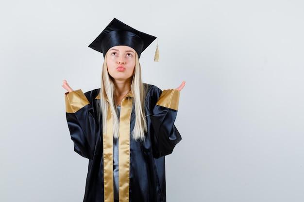Blondynka wyciąga ręce w pytający sposób, wykrzywia usta, patrzy w górę w sukni i czapce na zakończenie szkoły i wygląda na zamyśloną