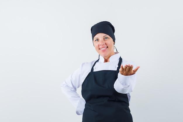 Blondynka wyciąga rękę do przodu, aby coś odebrać, trzymając drugą rękę na pasie w czarnym mundurze kucharza i ładnie wyglądającą.