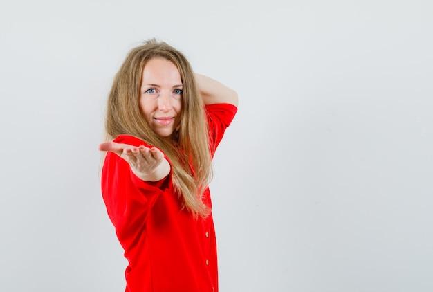 Blondynka wyciągając rękę i uśmiechając się w czerwonej koszuli