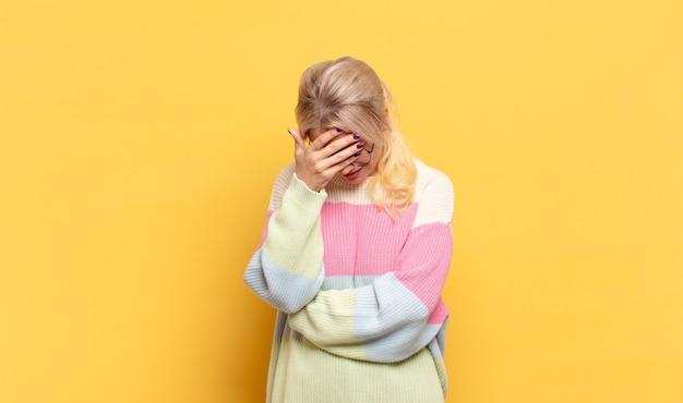 Blondynka wygląda na zestresowaną, zawstydzoną lub zdenerwowaną, z bólem głowy, zakrywa twarz dłonią