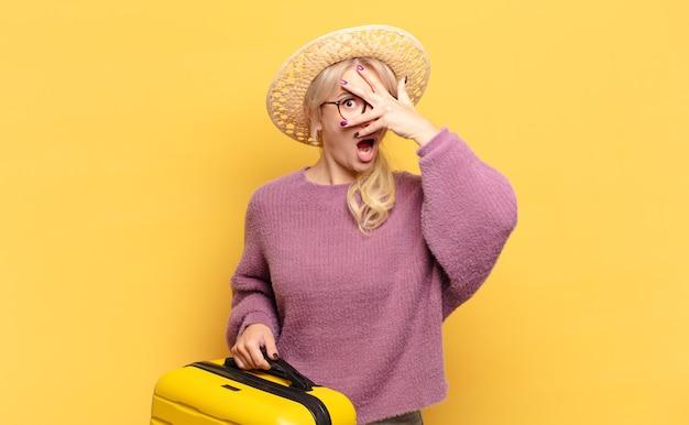 Blondynka wygląda na zszokowaną, przestraszoną lub przerażoną, zakrywa twarz dłonią i zerka między palcami